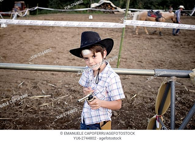 7 year old boy with country hat and toy gun