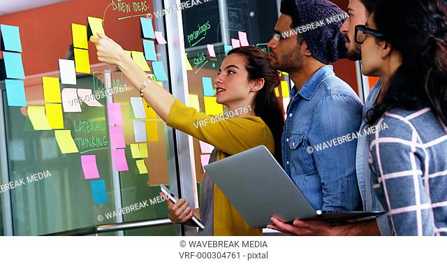 Smiling executives discussing over sticky notes on glass wall