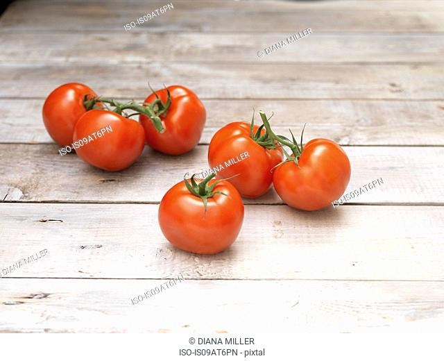 Six red vine tomatoes on wooden table