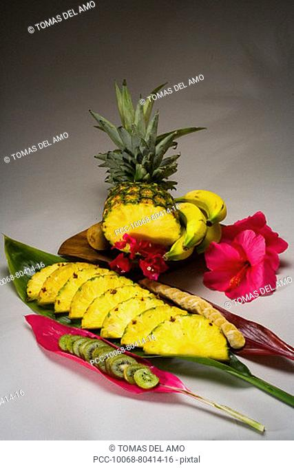 Studio shot of a pineapple, kiwi and bananas, cut into slices