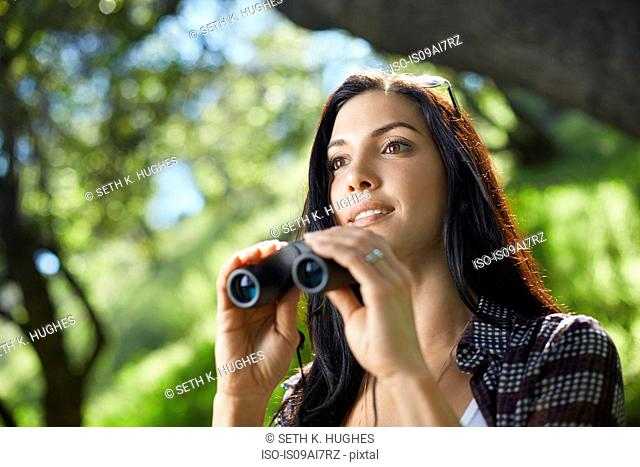 Mid adult woman with binoculars birdwatching in forest