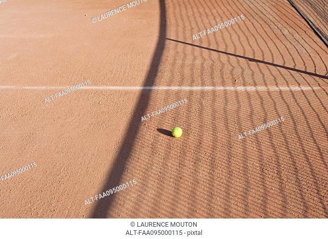 Shadow of net in tennis court over tennis ball