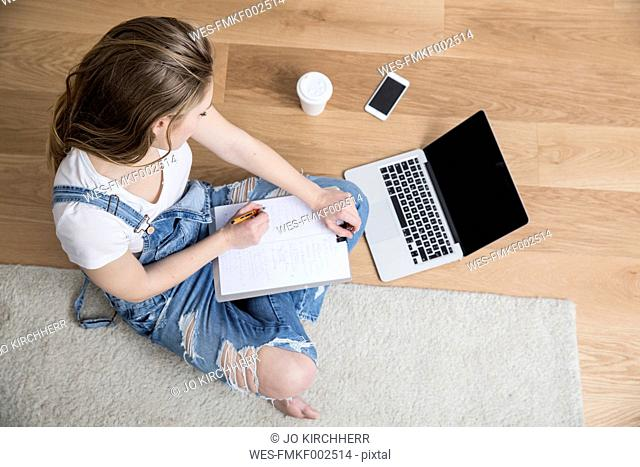 Young woman sitting on the floor with laptop and clipboard making notes