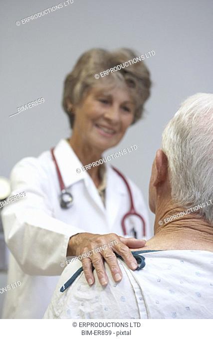 Senior female doctor reassuring senior male patient