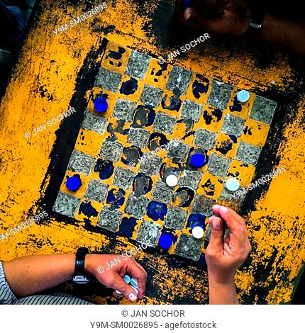 A hand of a Salvadoran man is seen before moving a plastic bottle cap while playing checkers on an outdoor checkerboard table in the park in San Salvador