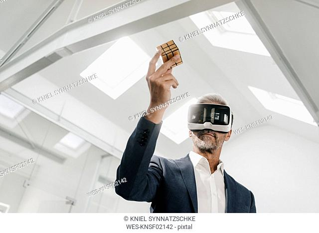 Mature businessman in office wearing VR glasses holding Rubik's Cube