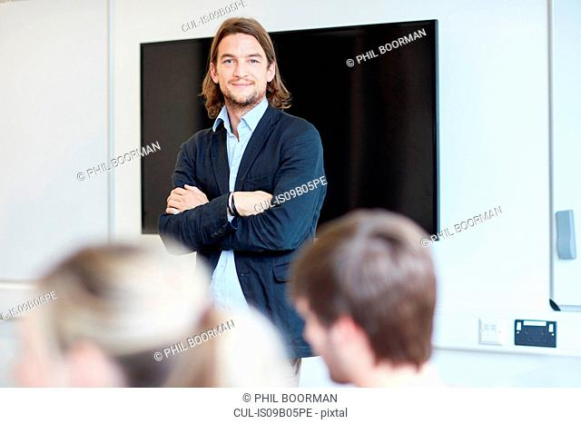 Portrait of male lecturer with arms folded in higher education college classroom