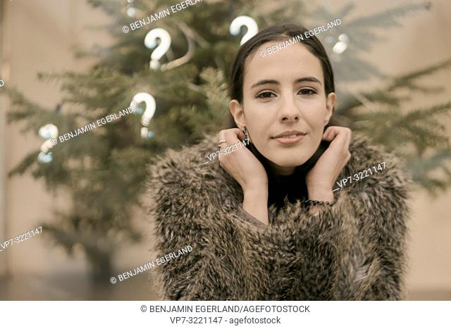 confident woman in front Christmas tree with lights of question marks, in Munich, Germany