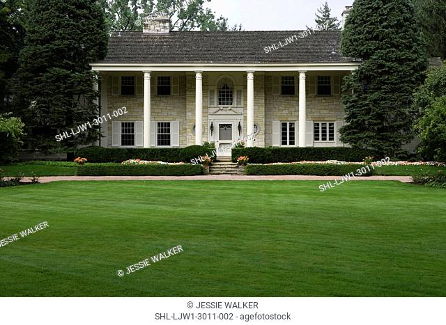 EXTERIORS: Lannonstone Colonial Revival, expansive lawns and manicured gardens in front of house, close up straight on, porch with tall columns across the front