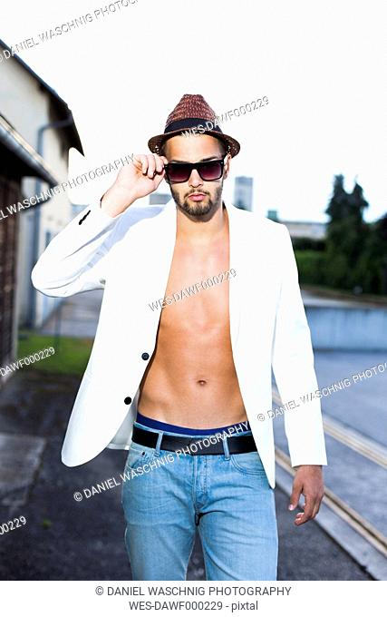 Young man wearing hat, sunglasses and white jacket on bare chest