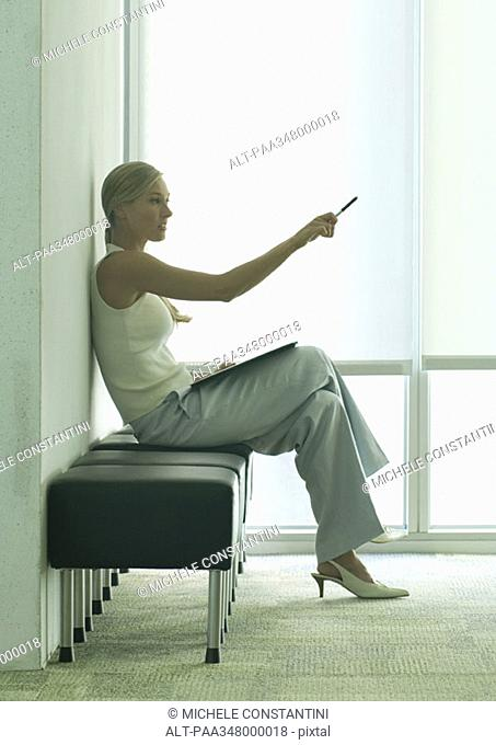 Woman sitting in office lobby, pointing