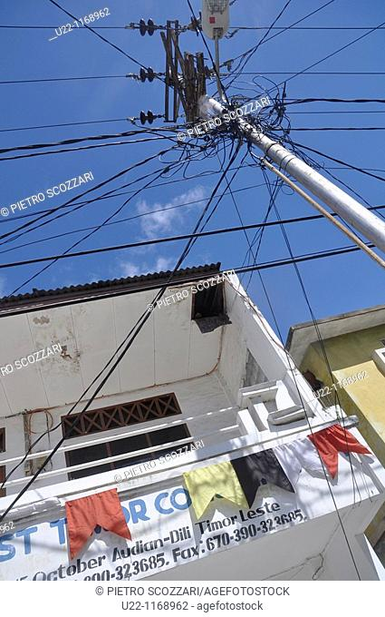 Dili (East Timor): an electricity pole and wires mess by a house
