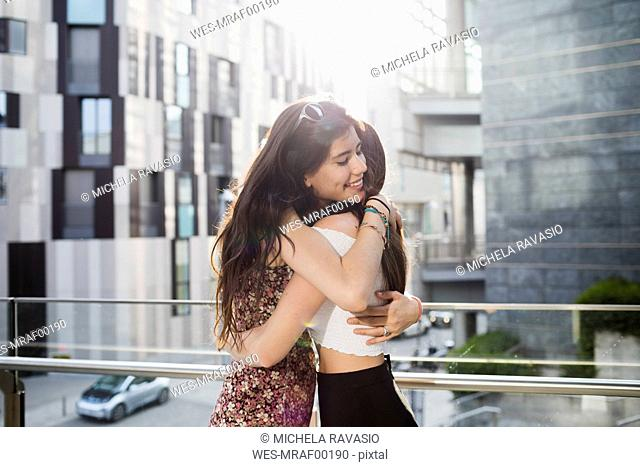 Two happy young women hugging in the city