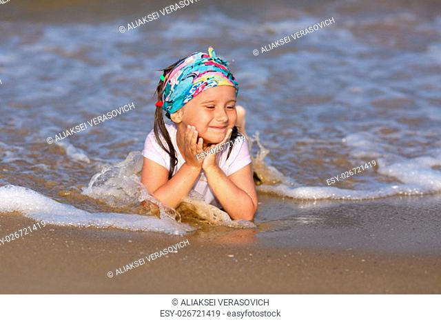 A child in a white t-shirt is in the water at the beach on a clear sunny day, his head in his hands