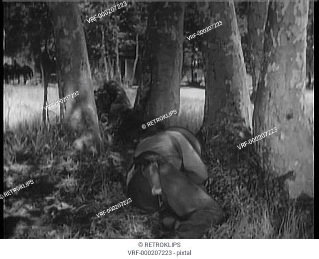 Rear view of cowboy reaching for gun during shootout