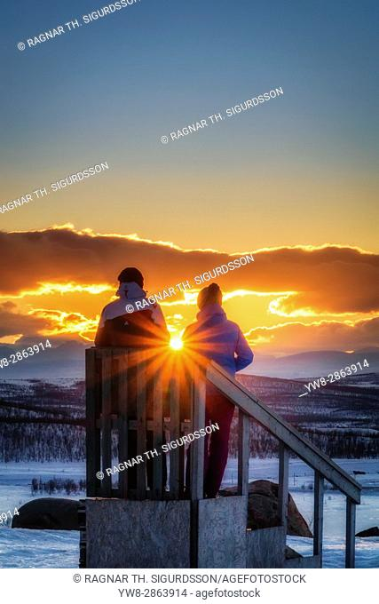 Couple enjoying a winter sunset, Lapland, Sweden