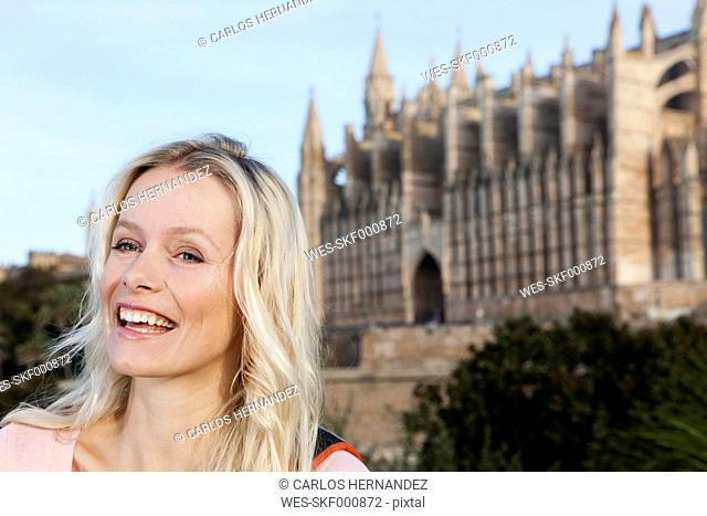 Spain, Mallorca, Palma, Young woman standing with St Maria Cathedral in background, smiling