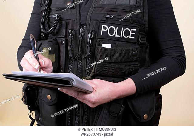 Police officer wearing tactical vest writing notes on a pad