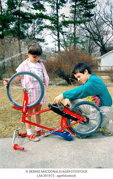 Brother helps younger sister fix a loose chain on her bicycle