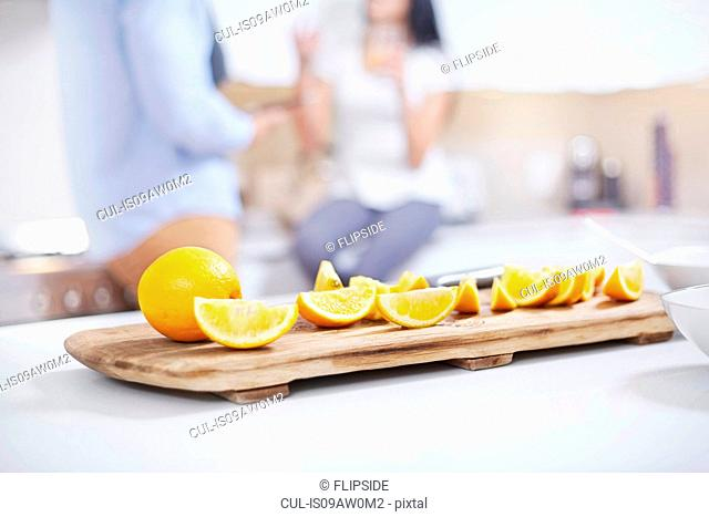 Quartered oranges on kitchen counter in front of young couple