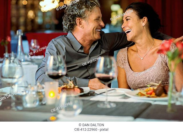 Happy mature couple sitting at restaurant table, wineglasses in foreground