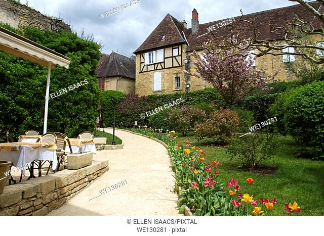 Tulips lining path from outdoor courtyard restaurant toward medieval sandstone buildings in charming Sarlat, Dordogne region of France