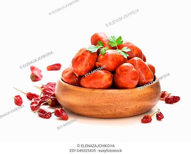 Mini chorizo sausages in wooden bowl isolated on white