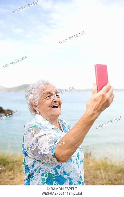 Happy senior woman taking selfie on the beach