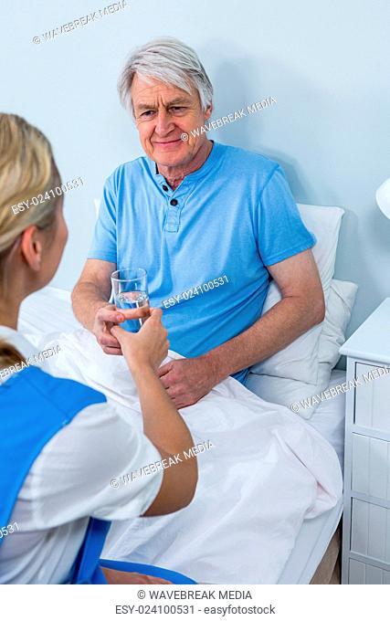 Nurse giving medicins to senior man at home