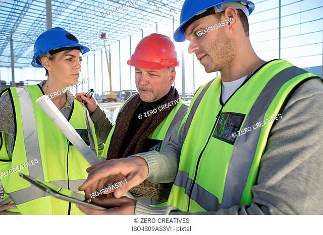 Surveyor and builders using digital tablet on construction site