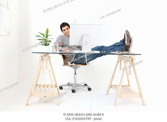 Man working at computer with his feet up