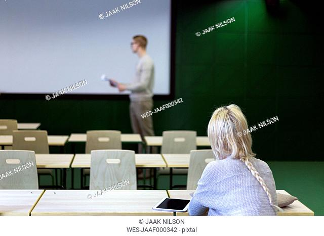 Young woman in classroom looking at lecturer