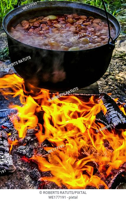 Cooking soup in cast iron boiler on burning campfire. Pot with soup over the open fire outdoors. Tourism in Latvia. Cooking soup in a pot on campfire