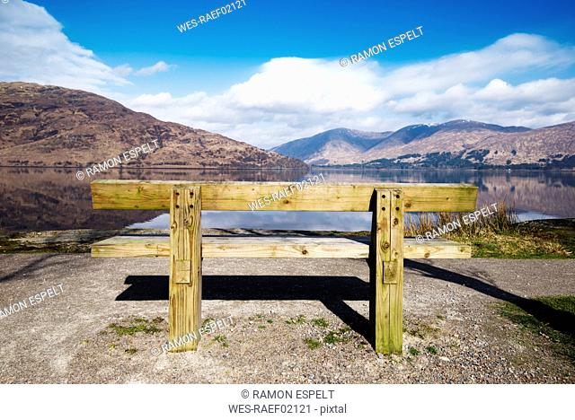 United Kingdom, Scotland, view of a loch, empty wooden bench