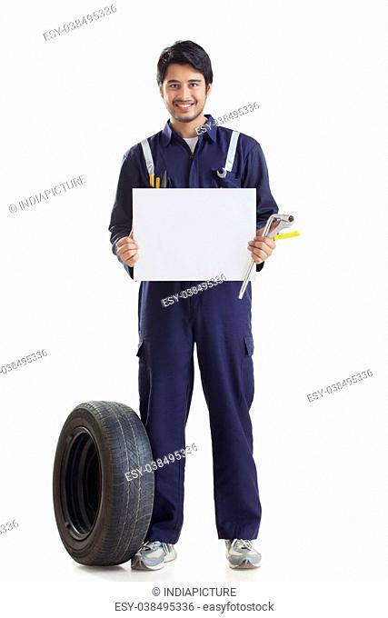 Portrait of mechanic holding blank card