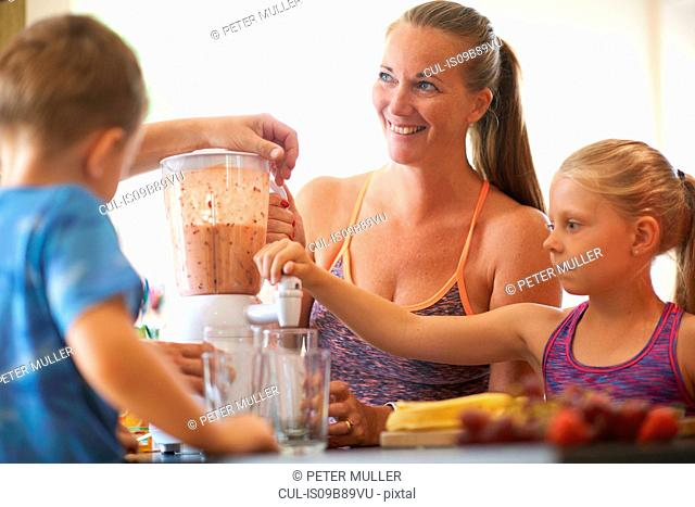 Mature woman and children blending fresh smoothie in kitchen