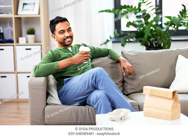 happy indian man drinking takeaway coffee at home