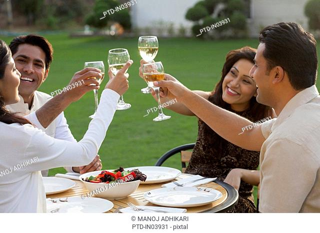 India, Friends toasting at table on backyard