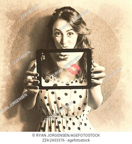 Modern meets vintage with an old fashion girl from the 1950s taking a selfie with electronic tablet device. Pin up girl with technology love