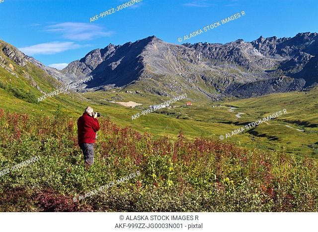 Male tourist photographing Hatcher Pass and Independence Mine buildings, Talkeetna Mountains, Southcentral Alaska, Summer