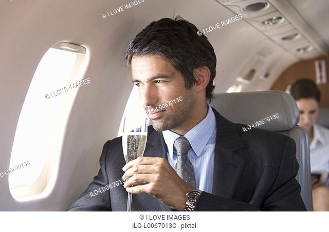 A businessman drinking champagne on a flight