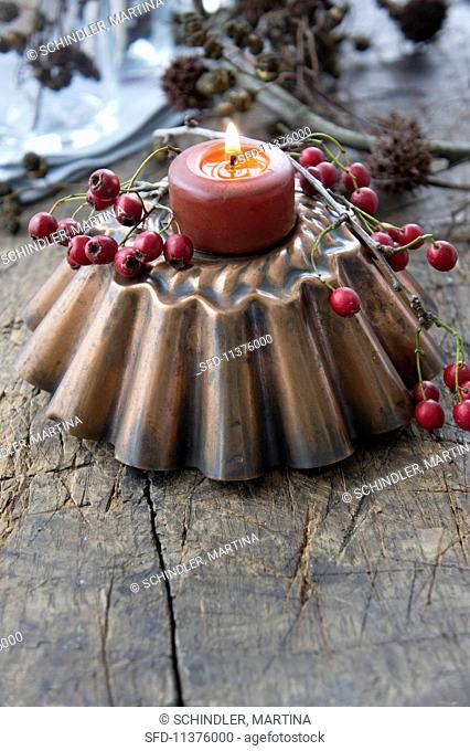 A baking tin with a candle and hawthorn berries