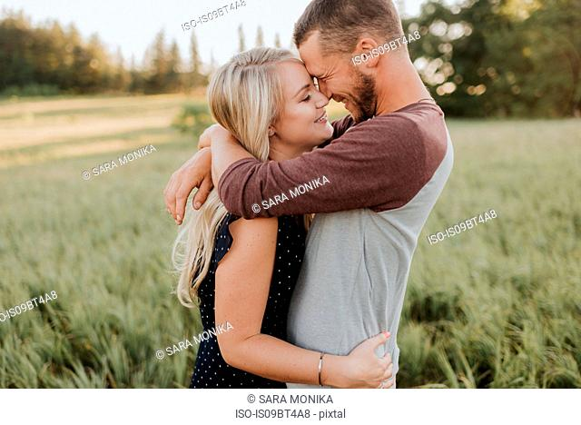 Romantic man and girlfriend hugging in field of long grass