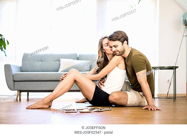 Happy affectionate couple sitting at home with photographies on the floor
