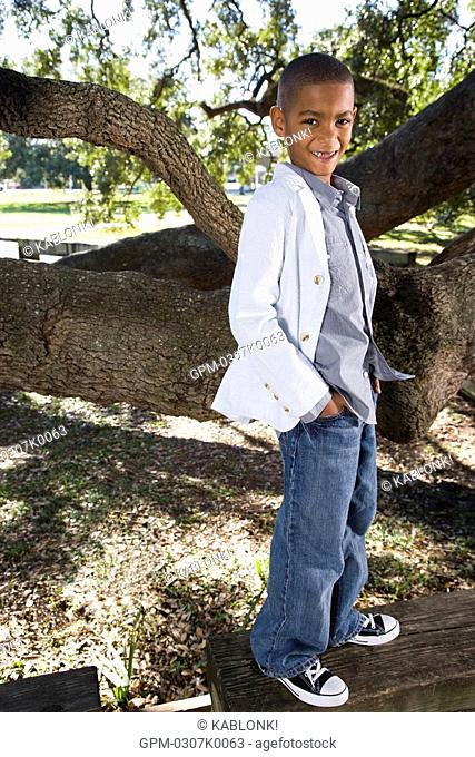 Portrait of African American boy standing in park near tree