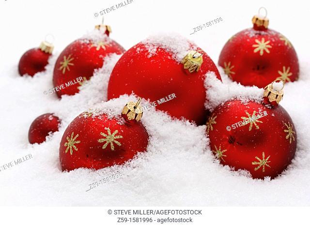 arrangement of christmas tree baubles on snow - shop window advertising