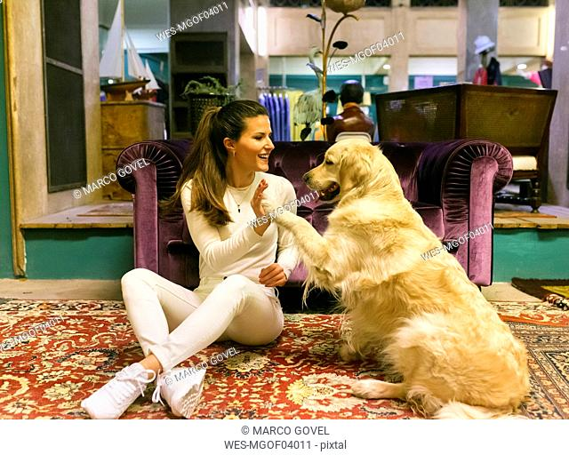 Smiling woman with dog sitting on carpet in a vintage shop
