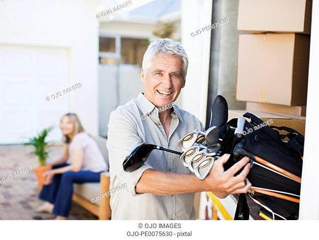 Man removing golf clubs from moving van