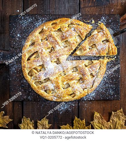 baked whole round apple pie on a rectangular old brown cutting board sprinkled with powdered sugar, top view