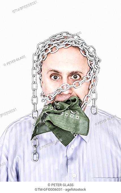 Bald man with chains on his head and a gag in his mouth